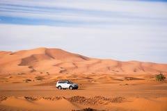 白色越野驾车在merzouga摩洛哥撒哈拉大沙漠  高沙丘在背景中 沙漠驾驶 探索越野 免版税库存图片