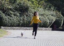 白色跑在公园的狗和一个俏丽的女孩 免版税库存图片