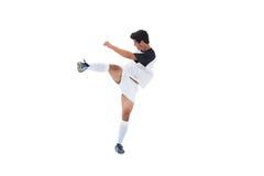 白色踢的足球运动员 免版税库存照片