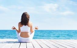 白色运动的衣裳的妇女思考在一个木码头的在夏天 海和天空背景 瑜伽,体育,假期 库存照片