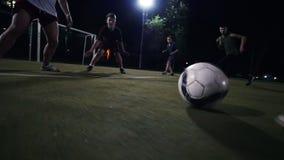 白色运动鞋的足球运动员移动与在领域,另一次球员攻击,夜射击的球 股票录像