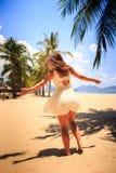 白色连衣裙的亭亭玉立的女孩摆在用在旁边手在海滩 图库摄影
