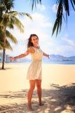 白色连衣裙的亭亭玉立的女孩摆在用在旁边手在海滩 库存图片