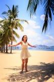 白色连衣裙的亭亭玉立的女孩摆在用在旁边手在海滩 免版税库存图片