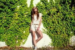 白色连裤外衣、keds和时髦回合的美丽的轻松的妇女反映了站立在墙壁的太阳镜纠缠与常春藤 库存图片