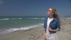 白色透明礼服的年轻性感的妇女有白发的飞行在风享用太阳的由海 股票录像