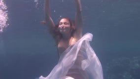 白色透明面纱的水下的式样女孩自由的潜水者在红海 影视素材