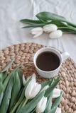白色郁金香和一杯咖啡花束在桌上的 舒适家 图库摄影