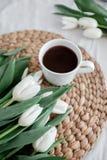 白色郁金香和一杯咖啡花束在桌上的 舒适家 库存照片