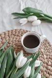 白色郁金香和一杯咖啡花束在桌上的 免版税库存图片