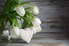 白色郁金香和木头心脏形状反对木的葡萄酒的 免版税库存图片