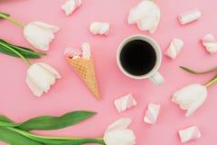 白色郁金香开花与杯子咖啡、蛋白软糖和奶蛋烘饼锥体在桃红色背景 博客作者概念 平的位置,顶视图 库存照片
