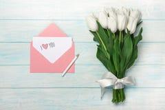 白色郁金香花束与爱笔记和颜色信封的在蓝色木板 免版税库存图片