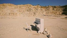 白色钢琴和一把白色椅子在黄沙站立以岩石为背景在日落 超现实的剧情 通风 影视素材