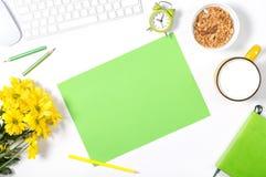 白色键盘、五颜六色的文具、黄色花、板材有格兰诺拉麦片的和大杯子牛奶在白色背景 图库摄影