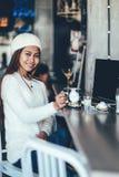 白色长的袖子饮用的茶的美丽的女孩在咖啡馆 库存照片