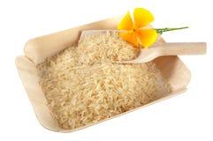 白色长粒米、瓢和黄色花在竹盘子 库存图片