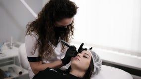 白色长袍的美容师有卷发的得出形状或做更正有针的眼眉妇女的 股票录像