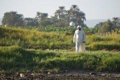 白色长袍的老人在尼罗的岸 免版税库存图片