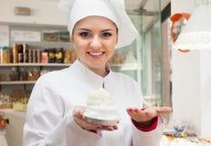 白色长袍的年轻厨师在糖果店显示用酥皮点心 免版税库存照片