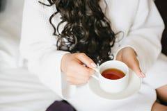 白色长袍饮用的茶的女孩 图库摄影