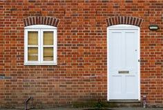 白色门和窗口在砖墙背景 免版税库存照片