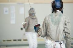 白色防护衣裳的两个少年击剑者战斗在操刀的比赛的 免版税库存照片