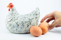 从白色陶瓷母鸡的劫掠鸡蛋 库存照片