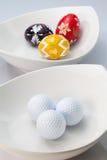 白色陶瓷碗、高尔夫球和鸡蛋 免版税库存照片