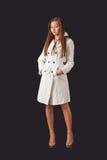 白色雨衣的年轻俏丽的妇女 免版税库存照片