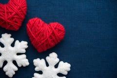 白色雪花和红色羊毛心脏在蓝色帆布背景 圣诞快乐看板卡 免版税库存照片