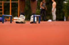 白色鞋子与人站立在两florr登上的蓝色把柄之间的橙色运动流动的表面上的腿,模糊 图库摄影