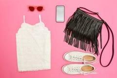白色鞋带上面、黑提包、白色运动鞋、玻璃和电话 明亮的桃红色背景 时兴的概念 免版税库存图片