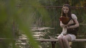 白色鞋带礼服的美丽的农村女孩由河坐木桥拥抱雄鸡,在自然的安静农村生活 影视素材