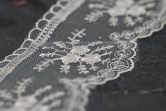 白色鞋带黑暗的表面上的被绣的边界 鞋带在深灰委员会的纹理背景 库存照片