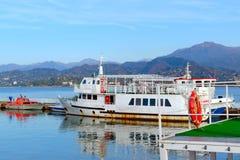 白色颜色一艘老游船与铁锈的在山的背景的口岸斑纹 免版税库存照片