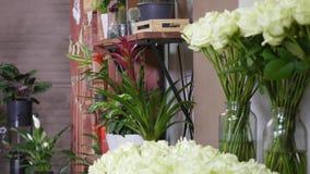 白色颜色新鲜的玫瑰特写镜头射击与绿色词根和叶子的在束安排了待售在花卉商店 免版税库存照片