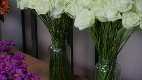 白色颜色新鲜的玫瑰特写镜头射击与绿色词根和叶子的在束安排了待售在花卉商店 库存照片