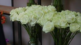 白色颜色新鲜的玫瑰特写镜头射击与绿色词根和叶子的在束安排了待售在花卉商店 免版税库存图片