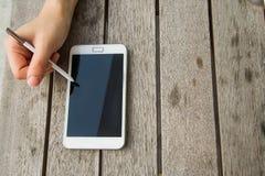 白色颜色智能手机woodden桌 免版税库存图片