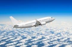 白色飞机在云彩蓝天上的天空飞行高 免版税库存照片