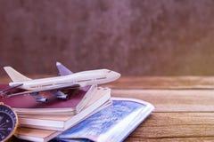白色飞机玩具、护照、地图和笔记本在一张木桌上 库存照片