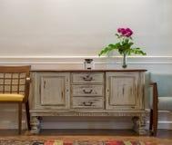 白色餐具柜的木葡萄酒,有红色花的玻璃花瓶,在白色墙壁上的两把椅子和木镶花地板 库存图片