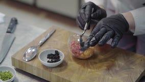 白色餐馆制服的厨师装饰有金枪鱼和selmon的一块板材和投入在一个黑鱼子酱里面 t 股票录像