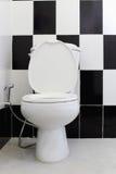 白色马桶在卫生间里 免版税库存图片