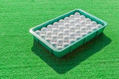 白色高尔夫球与绿草背景形成对比 免版税库存图片