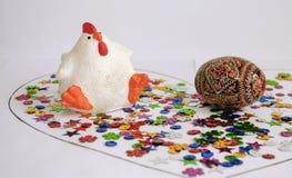 白色鸡和被绘的鸡蛋在五彩纸屑 图库摄影