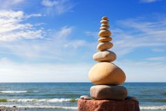 白色,圆的石头在蓝天和海背景平衡  图库摄影