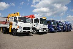 白色,有起重机胳膊的蓝色平板车卡车在停车场-俄罗斯,莫斯科, 2016年8月30日 免版税库存照片