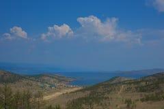 白色,蓬松云彩漂浮在青山的蓝天的和谷 免版税库存照片